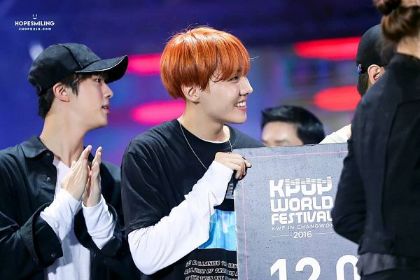 Tags: K-Pop, BTS, J-Hope, Jin, Grin, Clapping, Black Eyes, Red Hair, Two Males, Stage, English Text, Black Headwear