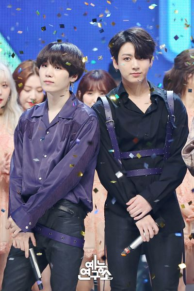 Tags: K-Pop, Television Show, BTS, Jungkook, Suga, Korean Text, Black Outfit, Collar (Clothes), Holding Object, Confetti, Black Pants, Blue Shirt