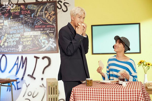 Tags: K-Pop, BTS, Persona (Song), J-Hope, Rap Monster, Two Males, Hat, Chalkboard, English Text, Table, Black Outerwear, Food