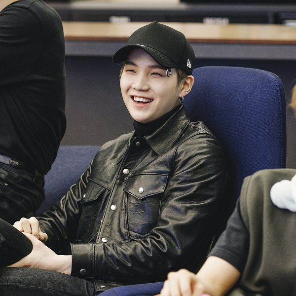 Tags: K-Pop, BTS, Suga, Hat, Collar (Clothes), Black Jacket, Black Headwear, Chair, Laughing, Turtleneck, Indoors, Jeans