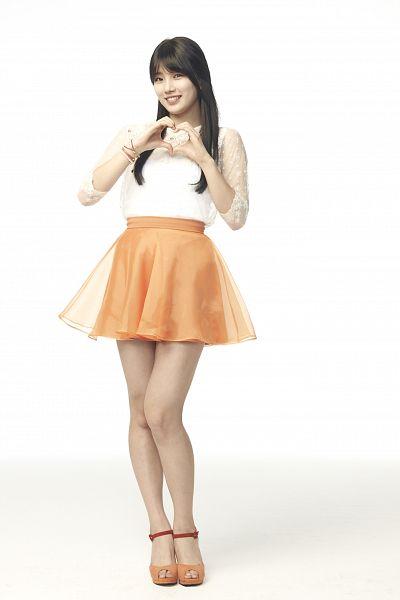 Tags: K-Pop, Miss A, Bae Suzy, Heart Gesture, Shadow, Orange Skirt, Bracelet, Blunt Bangs, Skirt, Light Background, Black Eyes, White Background