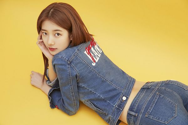 Tags: JYP Entertainment, K-Pop, Bae Suzy, Laying On Stomach, Denim Jacket, Yellow Background, Blue Pants, Laying Down, Jeans, Guess