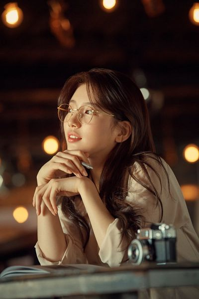 Tags: K-Pop, Bae Suzy, Sitting, Brown Shirt, Glasses, Looking Away, Camera, Bent Knees, Table, Pen, Carin