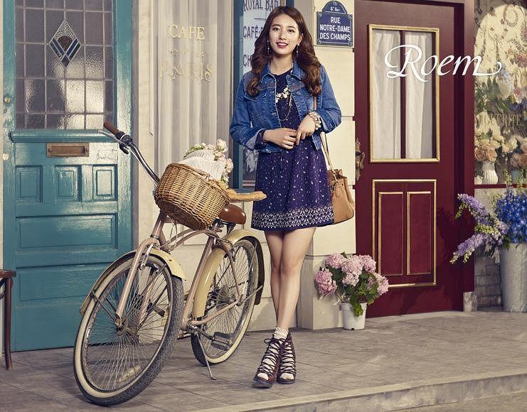 Tags: K-Pop, Bae Suzy, Green Flower, Table, Blue Outfit, Crossed Legs (Standing), Grin, Door, Vase, Red Lips, Bicycle, Wavy Hair