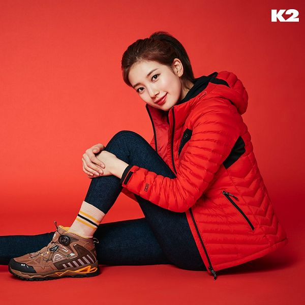 Tags: K-Pop, Bae Suzy, Brown Footwear, Ponytail, Red Jacket, Socks, Blue Pants, Red Background, Red Outerwear, Hand On Leg, Hand On Knee, Sitting On Ground