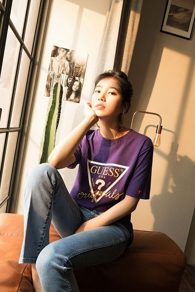 Tags: K-Pop, Bae Suzy, Hair Buns, Arm Support, Single Bun, Sitting On Couch, Purple Shirt, Short Sleeves, Hair Up, Plant, Black Eyes, Lamp