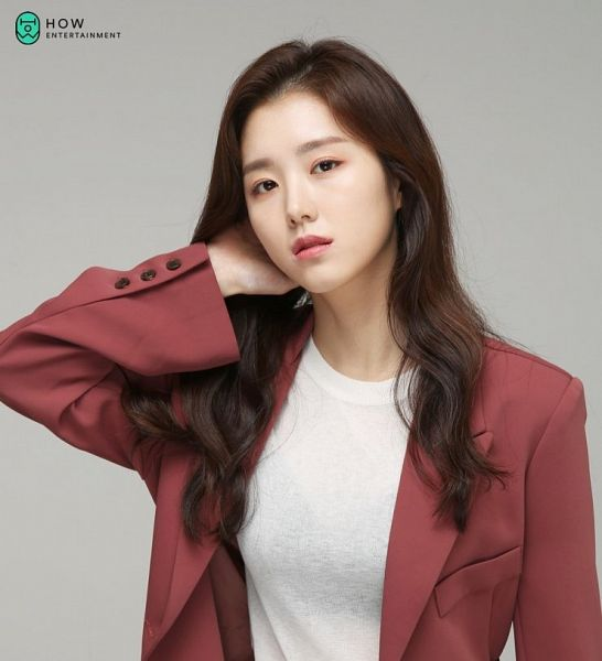 Tags: K-Drama, Baek Seo-e, Red Jacket, Red Outerwear, Gray Background, Hand On Neck, Serious