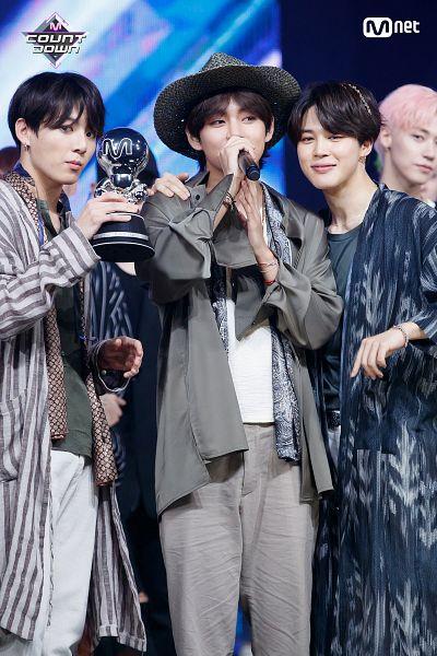 Tags: Television Show, K-Pop, Bangtan Boys, V (Kim Taehyung), Park Jimin, Jungkook, Pink Hair, Gray Jacket, Hat, Holding Object, Open Coat, Bracelet