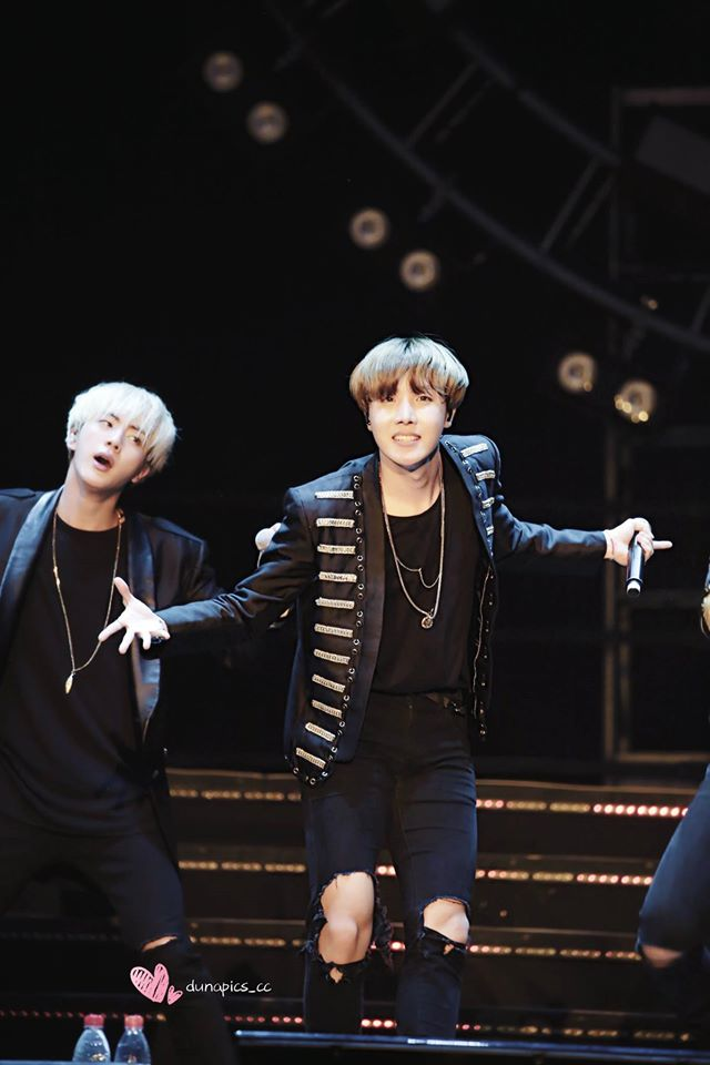 Tags: K-Pop, Bangtan Boys, J-Hope, Jin, Black Eyes, Black Jacket, Two Males, Grin, Black Shirt, Stage, Necklace, Black Outerwear