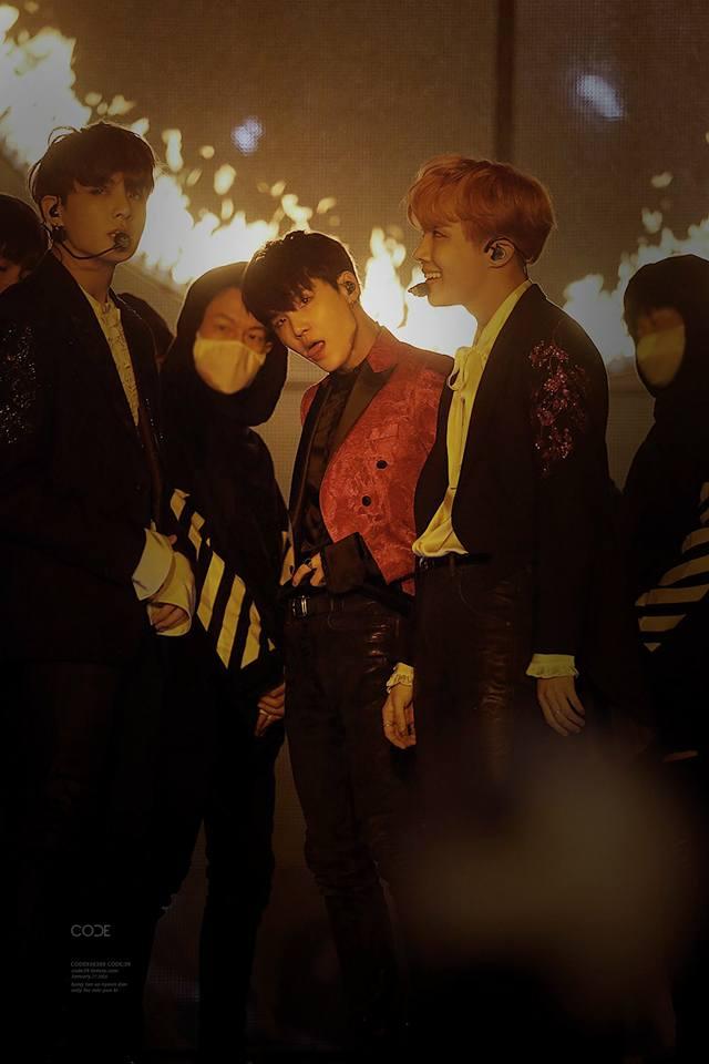 Tags: K-Pop, Bangtan Boys, Jungkook, J-Hope, Suga, Trio, Three Males, Black Eyes, Red Outerwear, Grin, Tongue, Stage