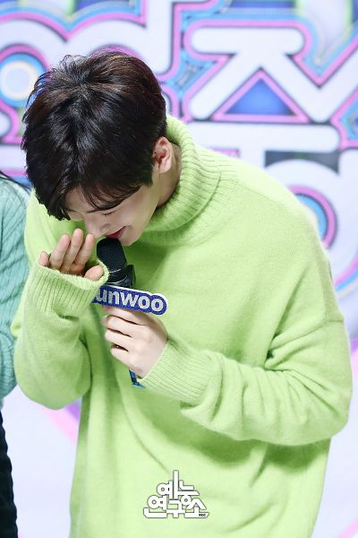Tags: K-Pop, Television Show, Astro, Cha Eunwoo, Eyes Closed, Turtleneck, Bend Over, Sweater, Holding Object, Korean Text, Laughing, Green Shirt