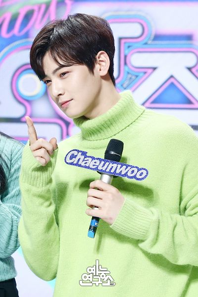 Tags: Television Show, K-Pop, Astro, Cha Eunwoo, Holding Object, Korean Text, English Text, Text: Artist Name, Green Shirt, Pointing, Turtleneck, Collar (Clothes)