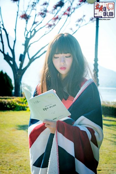 Tags: K-Drama, Chae Soo-bin, Reading, Tree, Text: Series Name, Plant, Pink Dress, Grass, Book, Blanket, Korean Text, Pink Outfit