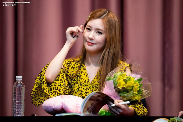 Tags: K-Pop, (G)-I-DLE, Cho Miyeon, Hair Ornament, Heart Gesture, Bottle, Holding Object, Curtain, Chair, Yellow Shirt, Pillow, Flower
