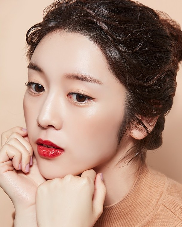 Tags: K-Drama, Choi Bae-young, Chin In Hand, Arm Support, Hair Up, Brown Background, Simple Background, Red Lips, A'pieu