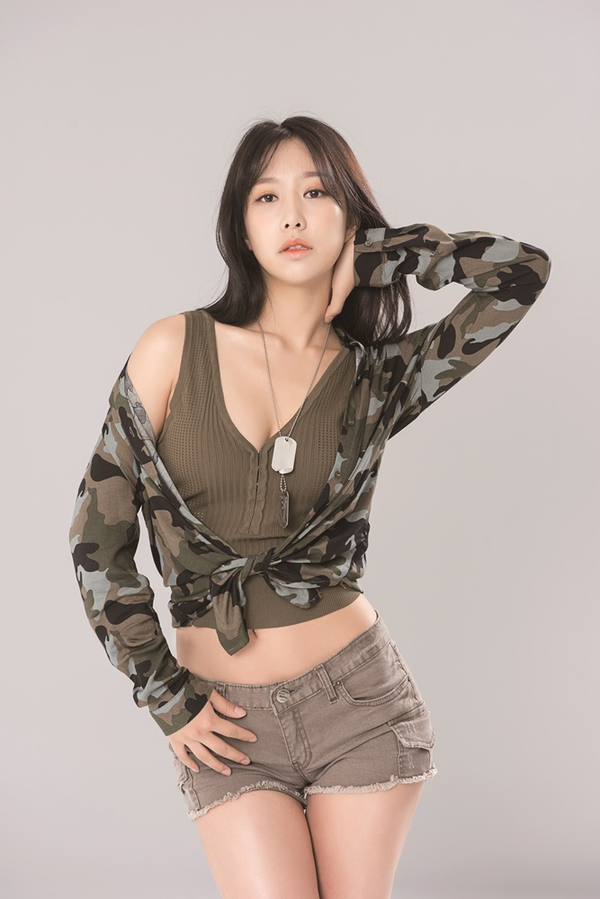 Tags: K-Pop, ICIA, Coca, Brown Shorts, Necklace, Brown Shirt, Crop Top, Camouflage Print, Gray Background, Hand On Neck, Serious, Midriff