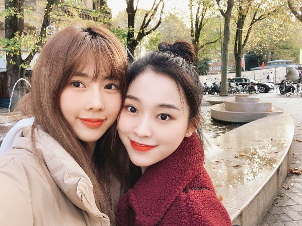 Tags: K-Pop, Dreamcatcher, Lee Gahyeon, Kim Yoohyeon, Hair Up, Red Outerwear, Duo, Brown Outerwear, Red Lips, Water, Tree, Red Jacket