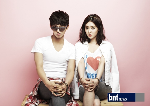 Tags: K-Drama, Lee Seul-bi, Oh Hyeok-won, Glasses, Sitting On Table, Pink Background, Sunglasses, Crossed Legs, Shorts, Gray Shorts, Duo, Bracelet