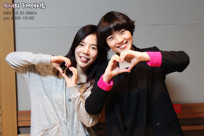 Tags: K-Pop, Girls' Generation, Ahn Young-mi, Sunny, Text: Series Name, Tongue, Black Jacket, Two Girls, Duo, Heart Gesture, Gray Shirt, Gray Background