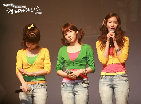 Tags: SM Town, K-Pop, Girls' Generation, Im Yoona, Sunny, Kim Tae-yeon, Trio, Yellow Outerwear, Jeans, Looking Down, Microphone, Green Outfit