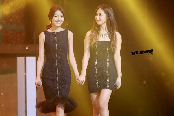 Tags: SM Town, K-Pop, Girls' Generation, Sooyoung, Kwon Yuri, Sleeveless Dress, Holding Hands, Wavy Hair, Two Girls, Walking, Brown Background, Necklace
