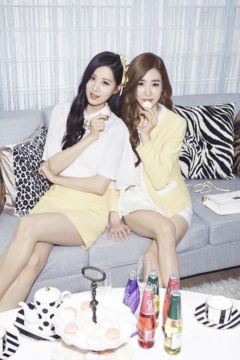 Tags: K-Pop, Girls' Generation, Seohyun, Stephanie Young Hwang, Yellow Outerwear, Light Background, Couch, Two Girls, Yellow Bow, White Background, Bare Legs, Skirt