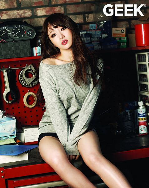 Tags: K-Pop, EXID, Hani, Brick Background, Bare Legs, Collarbone, Text: Magazine Name, Sitting On Table, Black Shorts, Shorts, Gray Shirt, Table