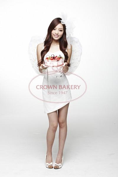 Tags: K-Pop, KARA, Hara Goo, Cake, Full Body, White Headwear, Wings, White Dress, Angel Wings, Gray Background, Wavy Hair, White Footwear