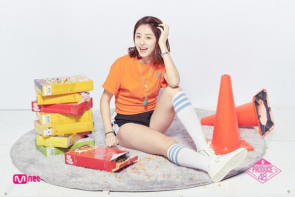 Tags: K-Pop, Television Show, Huh Yunjin, Tie, Holding Object, Sitting On Ground, Shorts, Orange Shirt, Hand On Cheek, White Footwear, Necklace, Text: Series Name