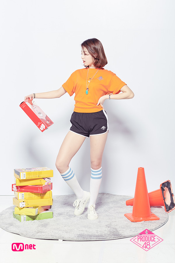 Tags: Television Show, K-Pop, Huh Yunjin, Thigh Highs, Black Shorts, Looking Away, Text: Series Name, Bracelet, Orange Shirt, Shoes, Tie, Hand On Hip