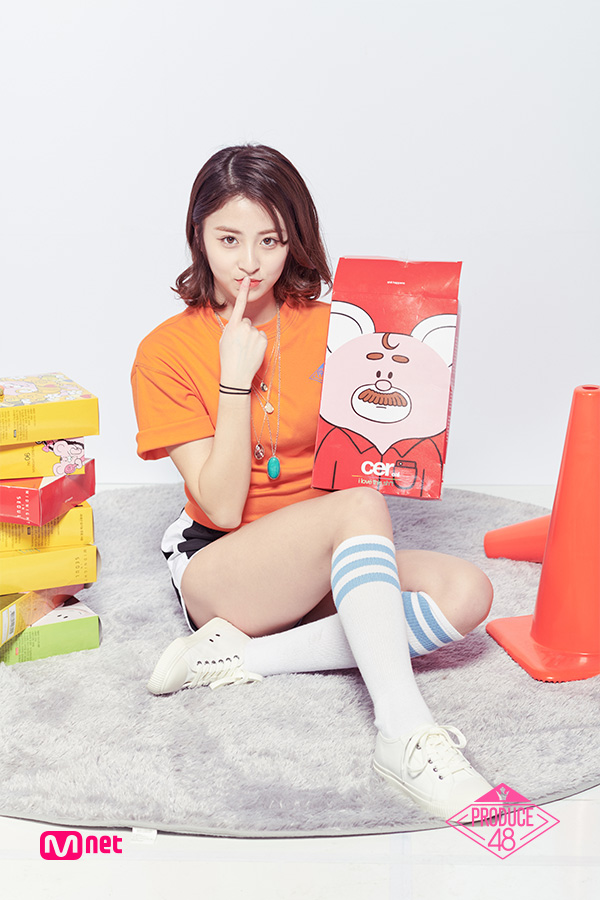 Tags: Television Show, K-Pop, Huh Yunjin, Bracelet, Orange Shirt, Shoes, Sitting On Ground, Tie, Shorts, White Footwear, Sneakers, Text: Series Name