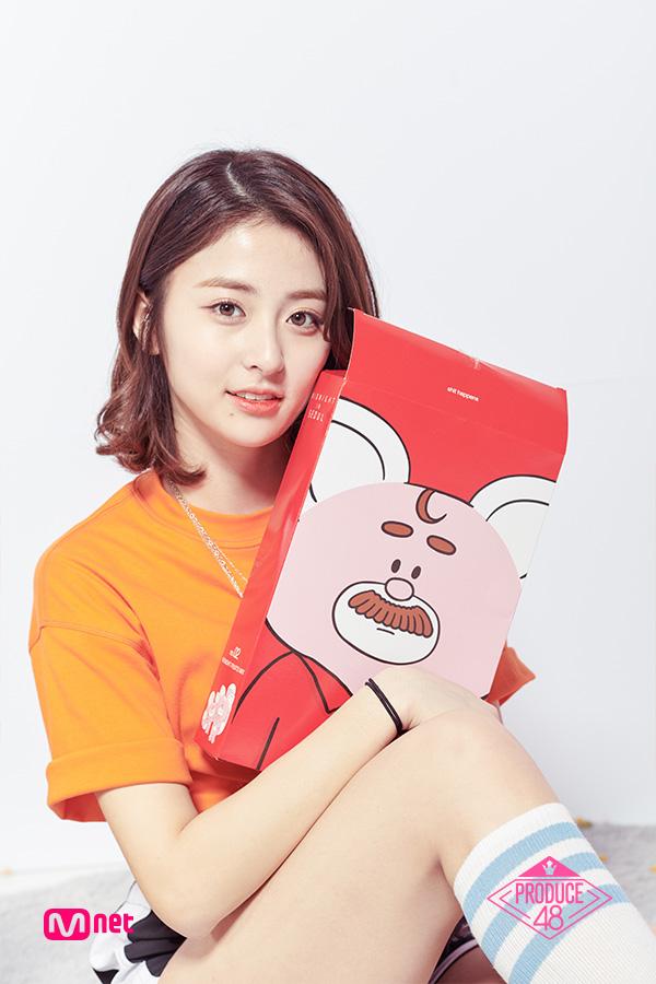 Tags: Television Show, K-Pop, Huh Yunjin, Box, Holding Object, Text: Series Name, Bracelet, Black Shorts, Close Up, Tie, Orange Shirt, Shoes