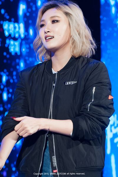 Tags: K-Pop, Mamamoo, Hwasa, Black Outerwear, Black Jacket, Hand On Arm, Medium Hair, Looking Ahead, Shorts, Blue Background, Jeans, Denim Shorts
