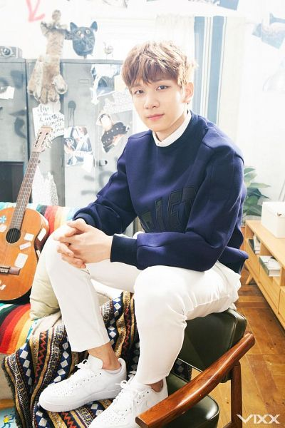 Tags: K-Pop, VIXX, Hyuk, Arm On Knee, Guitar, Sweater, Text: Artist Name, White Pants, Sitting On Chair, Clasped Hands, Shoes, White Footwear