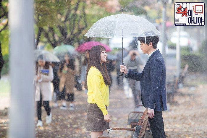 Tags: K-Drama, Chae Soo-bin, Um Ki-joon, Skirt, Duo, Bench, Yellow Shirt, Water, Looking At Another, Text: Series Name, Korean Text, Glasses