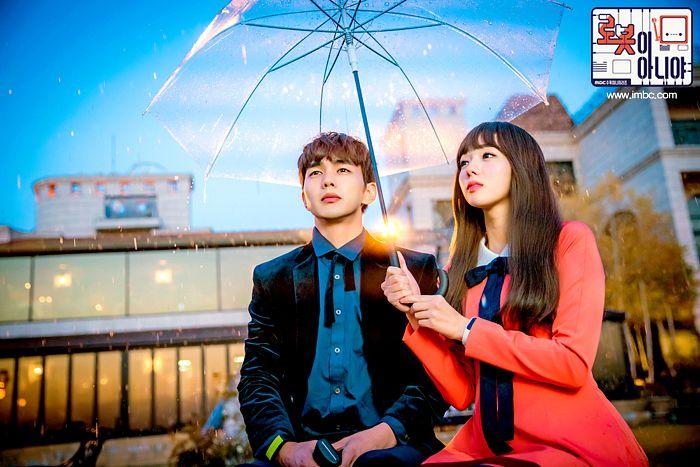 Tags: K-Drama, Yoo Seung-ho, Chae Soo-bin, Pink Dress, Umbrella, Text: Series Name, Serious, Duo, Water, Blue Shirt, Black Outerwear, Korean Text