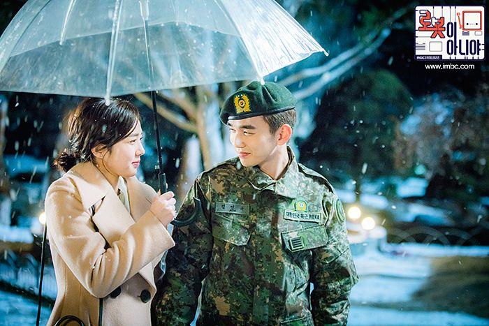 Tags: K-Drama, Chae Soo-bin, Yoo Seung-ho, Hair Up, Brown Outerwear, Snow, Korean Text, Looking At Another, Camouflage Print, Uniform, Umbrella, Ponytail