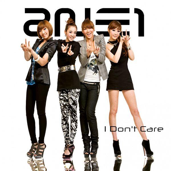 Tags: K-Pop, 2NE1, I Don't Care (2NE1), CL, Park Bom, Sandara Park, Minzy, Gray Jacket, Light Background, Belt, Text: Artist Name, Pointing