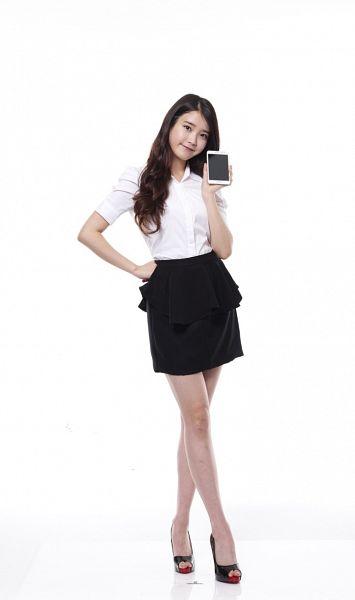 Tags: K-Pop, IU, Light Background, Short Sleeves, White Background, Crossed Legs (Standing), Hand On Hip, High Heels, Phone, Black Skirt, Skirt, Smartphone