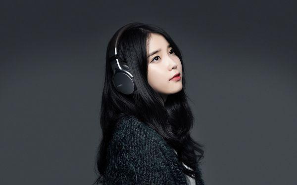 Tags: K-Pop, IU, Headphones, Dark Background, Wavy Hair, Black Outerwear, Looking Up, Sweater, Black Background, HD Wallpaper, Sony, Wallpaper