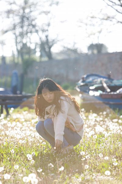 Tags: K-Pop, IU, Outdoors, Crouching, White Jacket, Wavy Hair, Grass, Looking Down, Jeans, Tree, Flower, White Outerwear