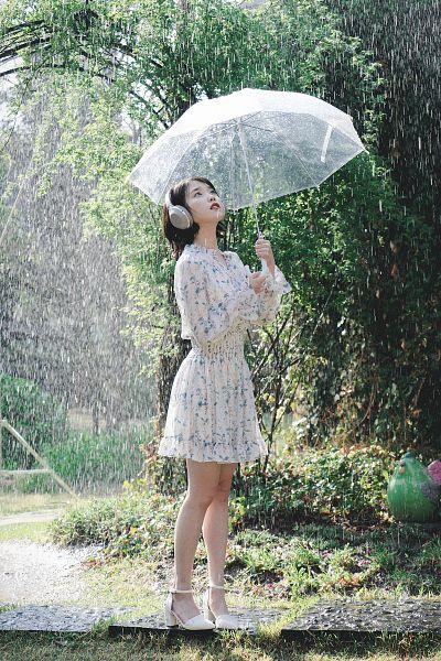 Tags: K-Pop, IU, Looking Up, Plant, Floral Print, Water, Rain, Headphones, High Heels, Serious, Umbrella, White Footwear