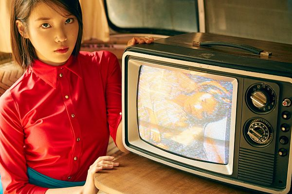 Tags: K-Pop, IU, Bent Knees, Table, Red Shirt, Sitting, Medium Hair, Television, Couch, Serious, Sitting On Couch, Skirt