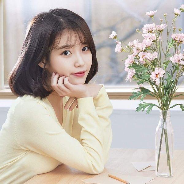 Tags: Loen Entertainment, K-Pop, IU, Table, Bottle, Arm Support, Yellow Shirt, Hand On Cheek, Facial Mark, Pink Flower, Medium Hair, Hand On Head