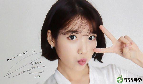 Tags: K-Pop, IU, Gray Background, Pouting, Facial Mark, Mole, Medium Hair, Korean Text, V Gesture, KDPharma