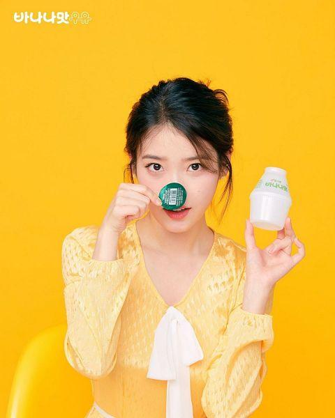 Tags: K-Pop, IU, Chair, Milk, Yellow Dress, Orange Background, Korean Text, Yellow Outfit, Hair Up, Drinks, Bottle, Eco Danji