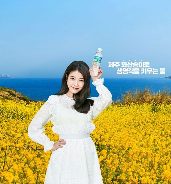 Tags: K-Pop, IU, Outdoors, Sea, Water, Flower, Yellow Flower, White Outfit, Sky, White Dress, Bottle, Hand On Hip