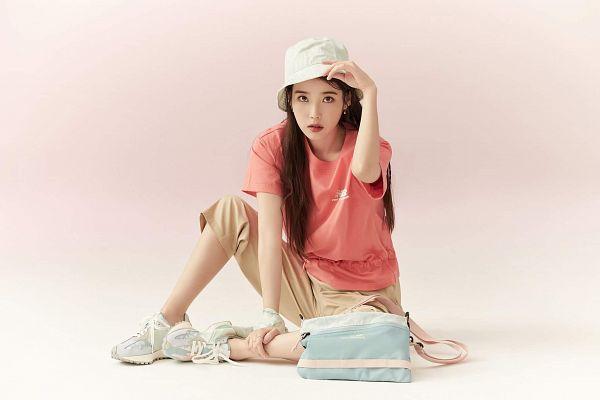 Tags: K-Pop, IU, Hand On Leg, Ring, Serious, Pink Shirt, Hat, Brown Pants, Short Sleeves, Pink Background, Bag, New Balance