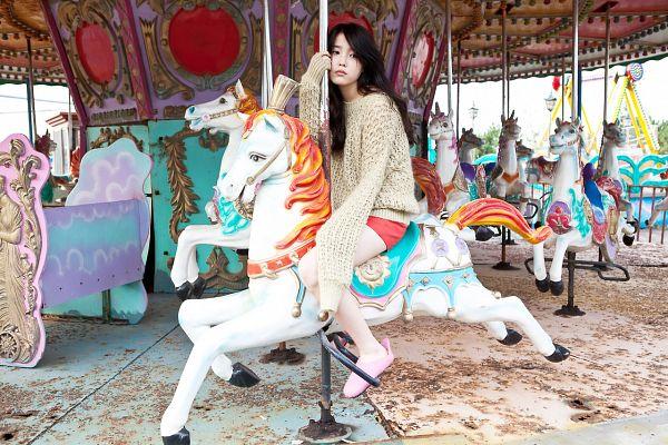 Tags: K-Pop, IU, Horse, Brown Shirt, Outdoors, Red Shorts, Sweater, Carousel, Looking Away, Pink Footwear, Looking Down, Amusement Park