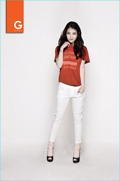 Tags: K-Pop, IU, Text: Brand Name, Orange Shirt, Hand In Pocket, White Pants, Bracelet, Short Sleeves, Guess